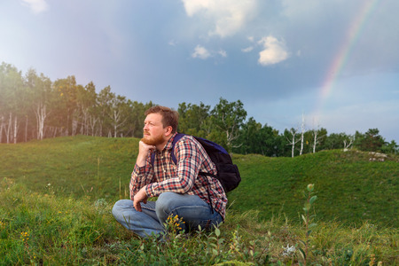 A man sits on a hill and watching the sunset. Tourist with backpack on green grass. Sun going down. A guy with a beard in a plaid shirt meets the sunset in nature. A lone traveler. Rainy clouds and a rainbow behind Stock Photo