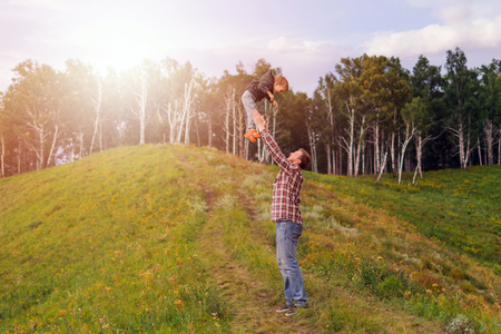 oneness: Father tossing up his son. The concept of oneness with nature, family relationships and values. Camping. Playing with your child. Flight and fun. Confidence