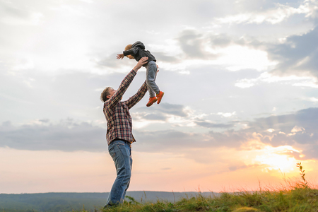 Father tossing up his son. High on a hill in the evening soltse. The concept of oneness with nature, family relationships and values. Camping. Playing with your child. Flight and fun. Confidence