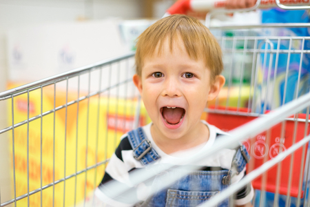 Boy sitting in a grocery cart and laughing, funny face, smile and curiosity, indulge and makes faces. Boy rides in a cart at the mall, at the grocery store