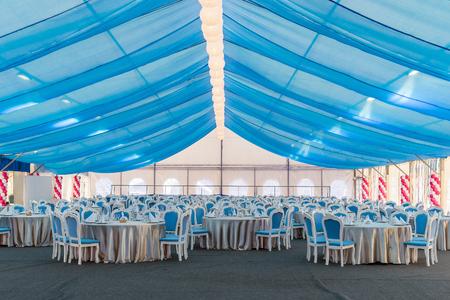 Eine leere Festsaal. Großes Zelt mit blauen Vorhängen, Tischen und Stühlen für eine große Anzahl von Gästen. Urlaub Dekoration, Dinner-Party. Standard-Bild