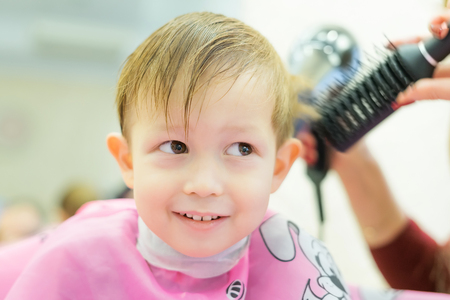 chub: The boy is cut in the hairdressers. A smiling child is sitting in the hairdressers salon. Female hands hold a comb and hair dryer. Drying hair on the head.