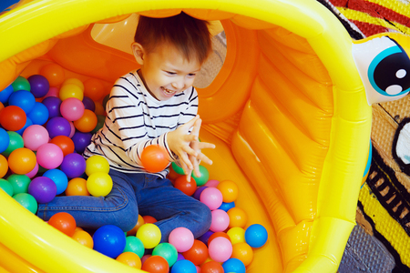 Boy playing with colored balls in the bouncy house at the Playground in the room. Colorful plastic balls, the joy on a childs face, a playful and funny guy. Foto de archivo
