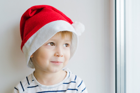 A boy in a red Santa Claus hat. The child smiles shyly and looks dreamily. Guessing a New Years gift