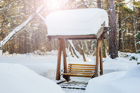 Wooden swing in the snow. Snow-covered forest with swings on the playground.
