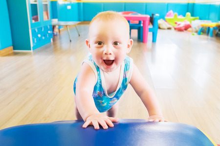 Charismatic kid plays in the childrens room. A smiling boy is playing in the playroom.