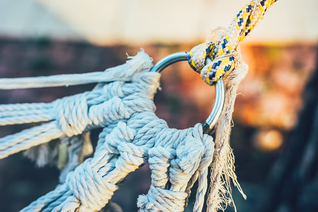 A knot of ropes and a ring. Bound ropes in dense strong knots. Hammock holder. Fasteners from ropes