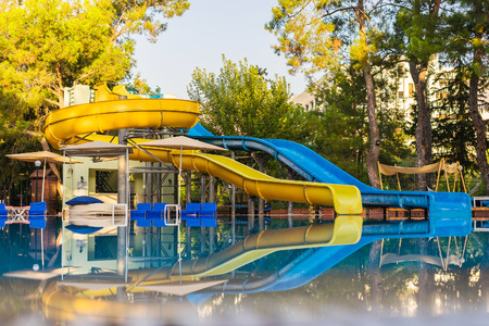 Water slides by the pool. Empty pool with water slides in the park.