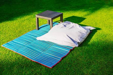 Pillow and coffee table on the grass. Rest area on the lawn. Stock Photo