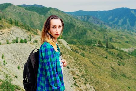 Tourist girl in the mountains. Girl breathes the mountain air and enjoys nature Banco de Imagens