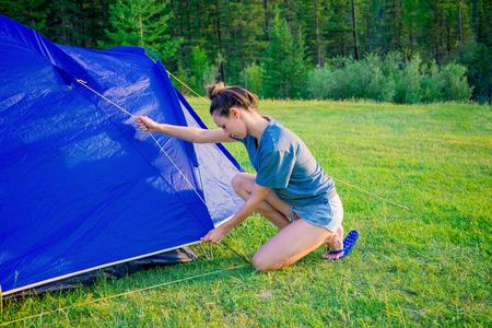 The girl sets up a tent on the grass. Tourist fortifies the tent, camping