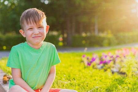 The boy sits grimaces and poses. Portrait of a preschooler. The boy sits in a park on a bed in the rays of the evening sun.