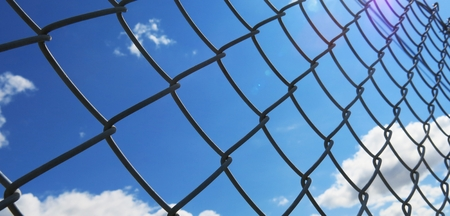 barbed wire fence with white clouds and blue sky background photo