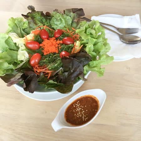 style: Japanese style salad mix green vegetables with sesame sauce on wooden table background