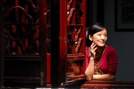 A Chinese girl lean on a triditional Chinese wooden window photo