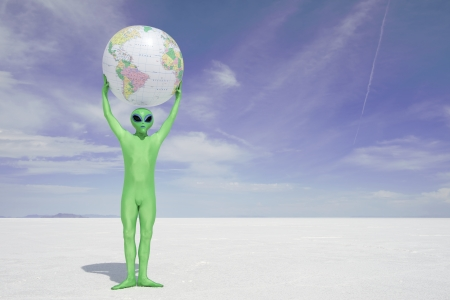 extraterrestrial: Green alien holds a globe of Earth above his head standing on desolate white desert planet Stock Photo