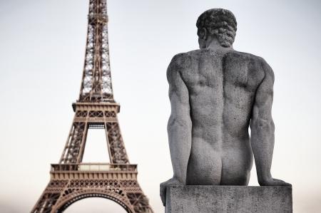 hombre sentado: Par�s, Francia Torre Eiffel de cerca con la estatua de piedra del hombre sentado en la parte posterior que mira el cielo atardecer Foto de archivo