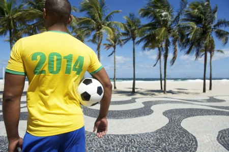 Brazilian soccer player holding football wears 2014 shirt in Brazil colors Rio de Janeiro photo