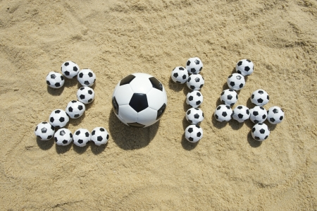 soccerball: Brazil 2014 World Cup message in football soccer balls on beach in Rio Stock Photo