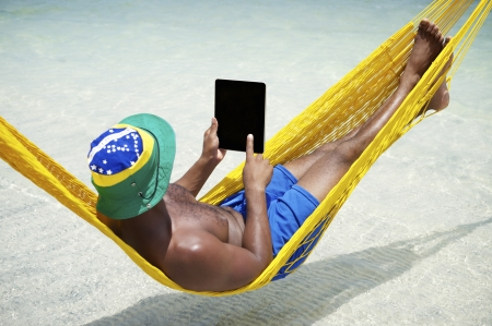 uses computer: Brazilian man uses tablet computer relaxing in hammock on beach over the sea Stock Photo