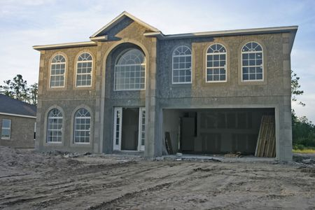 partially complete new home with concrete exterior and arched windows