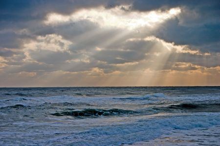 early morning rough sea conditions with sun rays creeping out of the overcast sky