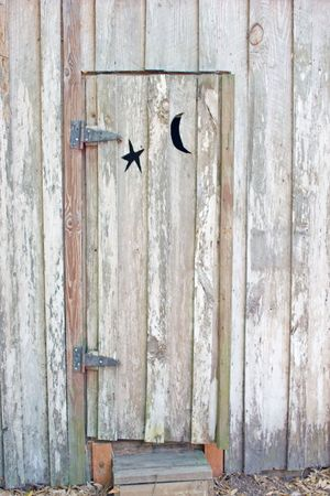 privy: door of vintage outhouse with moon and star cutour