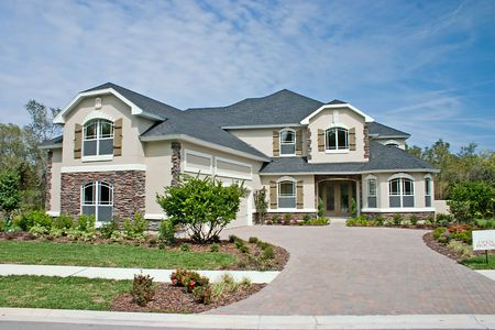 newly constructed luxury home with stone accents on front faces