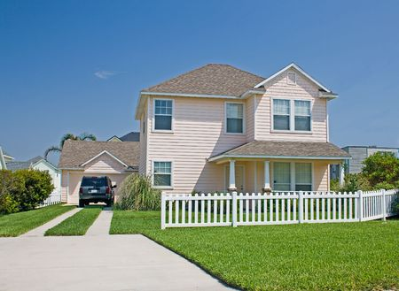 cottage fence: simple pastel pink Florida cottage style home with white picket fence