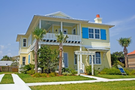 bright yellow coastal living home with bright blue shutters