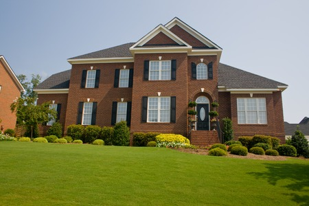 custom, upscale brick home with perfect green lawn Stock fotó
