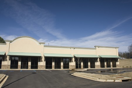 beige strip mall with green awnings and parking lot