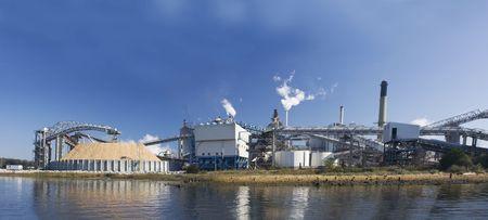 大規模な木材チップ ストレージ杭とリバー フロント フロリダ州製紙工場