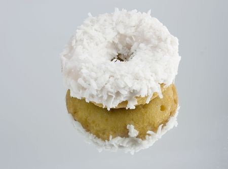 coconut cake doughnut with reflection on mirrored surface