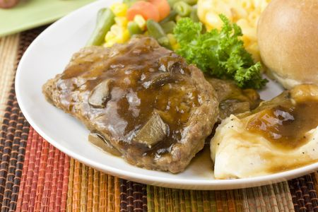 closeup of meatloaf slices with mushroom gravy, mashed potato, and vegetable medley