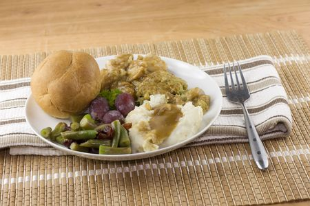 sliced turkey dinner with stuffing, green beans, mashed potatoes and a roll