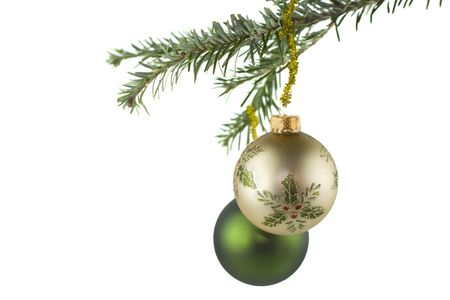 gold Christmas ornament with holly accents on fir tree  photo