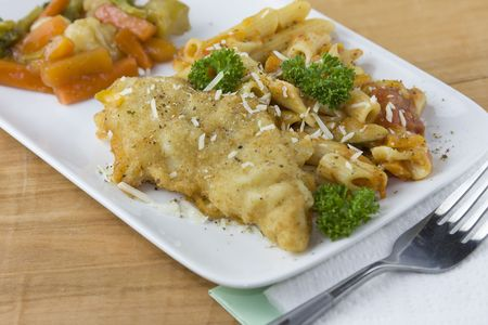 closeup of parmesan crusted fish with penne pasta and vetetables