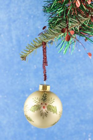 gold holly Christmas ball hanging from fir branch with green and red garland Stock Photo