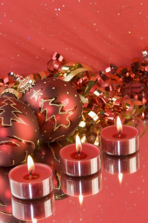 tealight: three christmas tealight candles with red baubles and curly ribbon Stock Photo