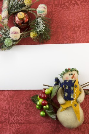 blank Christmas card with snowman, berry accent, frosted foliage, red bauble and copyspace