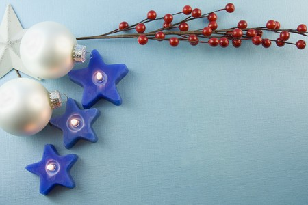 three Christmas star shaped candles with white baubles, holly berries on a soft blue background with copyspace Stock fotó