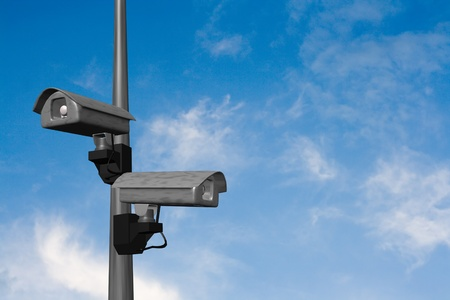 two security cameras on a lightpole with blue sky photo