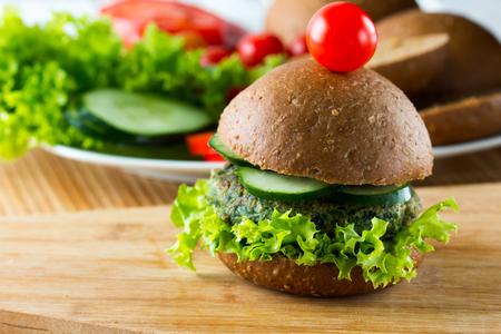 comiendo pan: hamburguesas de espinacas vegetariana con pan de centeno, el pepino y la lechuga, de cerca. horizontal Foto de archivo