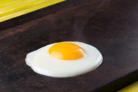 Fried ciken egg on the cast iron. Close up Stock Photo