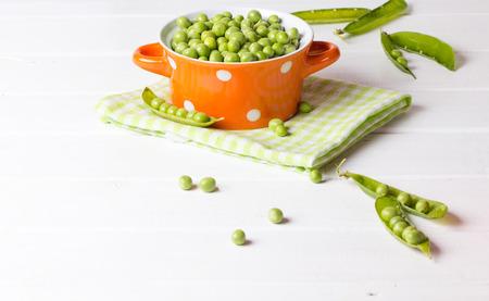 ingridients: Green peas in orange bowl on wooden white background