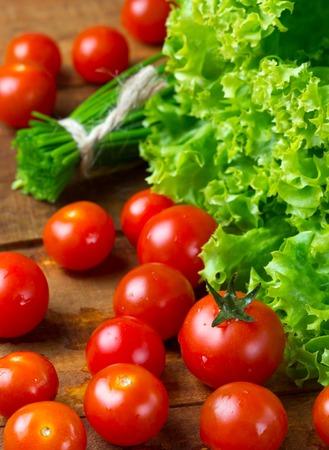 lechuga: ensalada de lechuga, tomate y cebolla verde sobre fondo oscuro de madera. vertical. de cerca