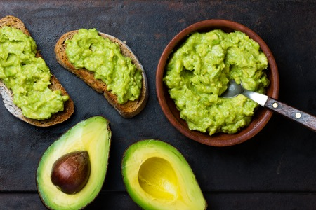 latinamerican: Traditional latinamerican mexican sauce guacamole in clay bowl and avocado sandwiches on dark background. Top view Stock Photo