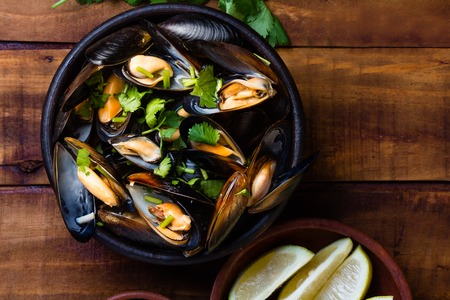 almejas: Mussels in clay bowl and lemon on wooden dark background Stock Photo