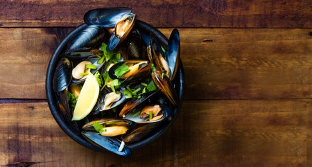 sopa: Mussels in clay bowl and lemon on wooden dark background Stock Photo
